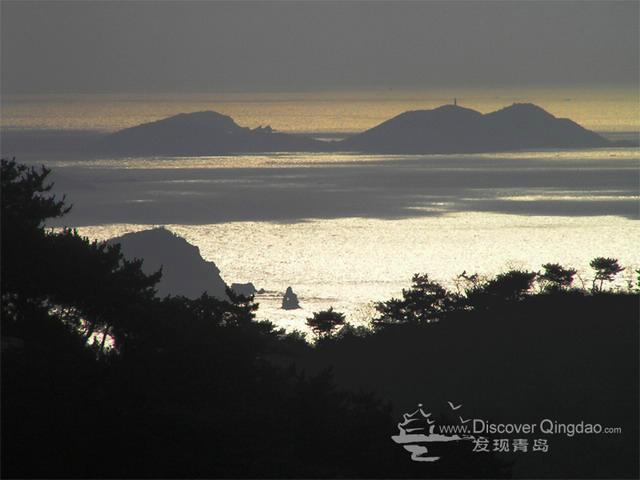 晨登浮山,阳光弱弱地洒向海岸,石老人在阳光辉映的海面上轮廓清晰.